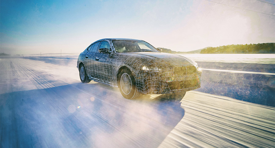 The camouflaged all-electric BMW i4 driving in the snow