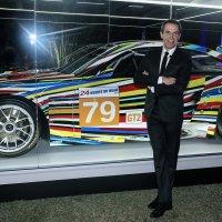 Jeff Koons standing in front of BMW Art Car he helped create.